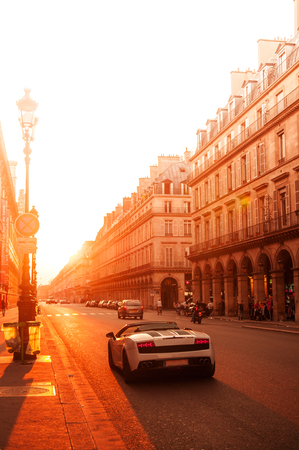 Paris street, French building and super car at sunset