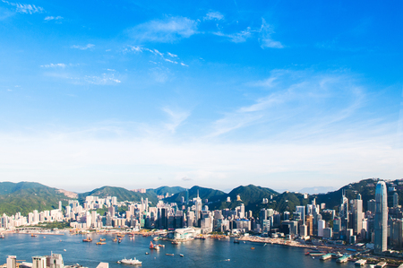 Aerial view of Hong Kong pier, boat and cityscape clear blue sky