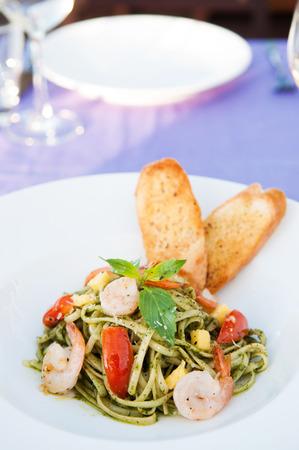 Linguine pasta with pesto sauce shrimps and tomato