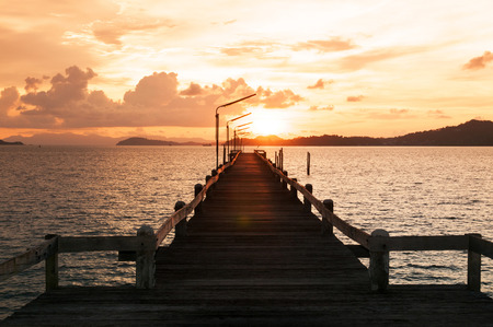 Sunset and wooden pier in Ranong province bay, Thailand. Stock Photo