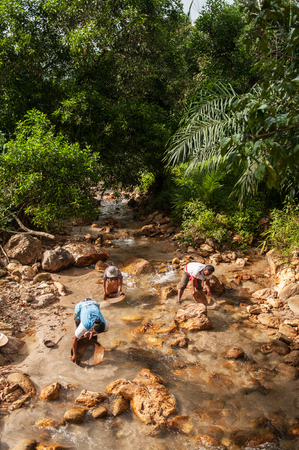 Local people do gold or tin panning in a river Stock Photo