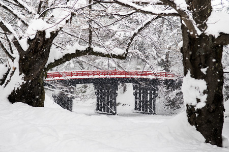 冬シーズン、青森、東北、日本の弘前の古いの赤い木製橋城雪の中に落ちる