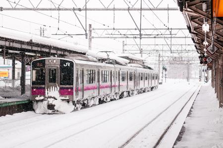 JAN 21, 2014 Hirosaki, Aomori, Japan : Pink strip JR East 701 Series commutor train at Hirosaki Station in winter, EMU train opperated on Ou Main Line between Akita and Aomori