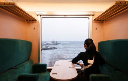 JAN 21, 2014 Aoike, Japan : Interior of East Japan Railway Gono line resort Shirakami sightseeing train in winter. Female Passenger sit in private seat with Japan sea scenery.