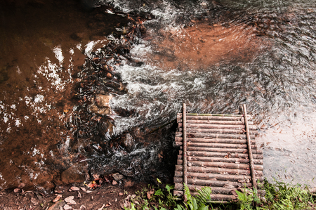 Rustic old wooden platform over rush water stream in forest. Shot from top angle 写真素材