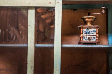 bronze, wooden old vintage coffee grinder in a cupboard