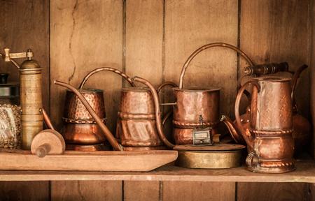 Copper, Brass old vintage tea pots and jars in wooden cupboard