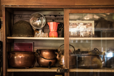 Wooden, copper, metal old vintage pots, jars and coffee pot in a cupboard 写真素材
