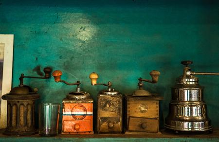 Wooden, bronze, metal old vintage coffee grinder on green background