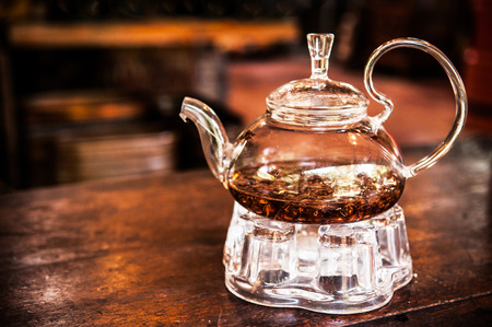 Glass teapot with tea leaves on wooden table and dark background in warm light 写真素材