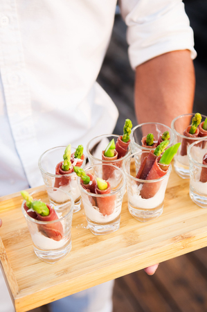 Canape from asparagus and dried ham with creamy sauce in glass serving by waiter on wooden tray Stock Photo