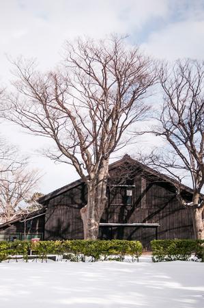 冬の雪の中のヴィンテージ古い日本の黒い倉庫、酒田サンキョーソーコ、山形鉱石、日本