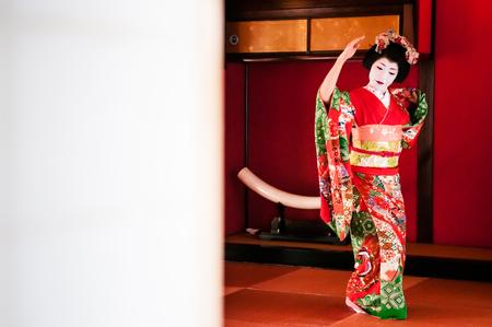 JAN 23, 2014 : Sakata, Yamagata, Japan : Japanese Maiko, Geisha in red costume, traditional entertainer performs dancing show in Tatami floor room, rich culture of Japan. Editorial