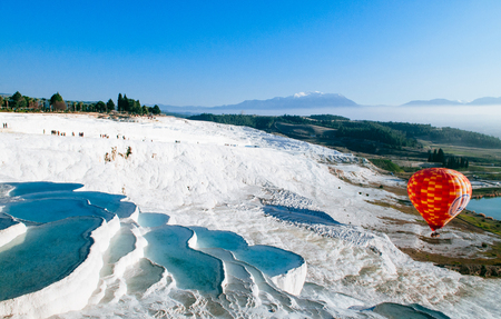 Hot air balloon flying over Travertine pools limestone terraces on beautifulday in Pamukkale, Denizili, Turkey Imagens - 94391751