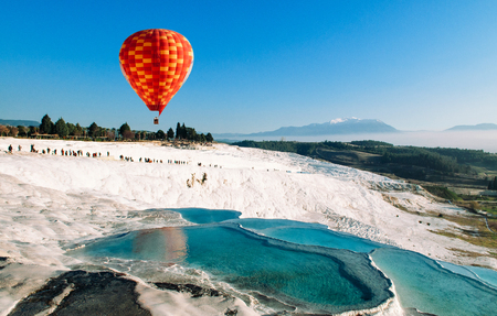 Hot air balloon flying over Travertine pools limestone terraces on beautifulday in Pamukkale, Denizili, Turkey