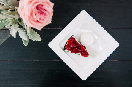 Fresh yummy Cherry cheesecake with pink rose Shot from top on black wooden table background. 写真素材