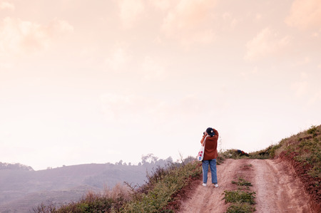 FEB 3, 2018 Chiang Mai, Thailand : Young woman taking photo of sunset sky on dirt path country road on the hill at evening in Chiang Mai 報道画像