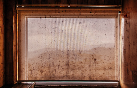 Very Old dirty grunge curtain in wooden cabin with black mold fungus and mountain view 写真素材
