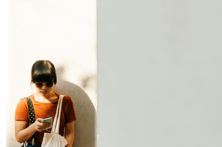 Young asian woman wearing sunglasses and using mobile phone under sunlight with white concrete wall background