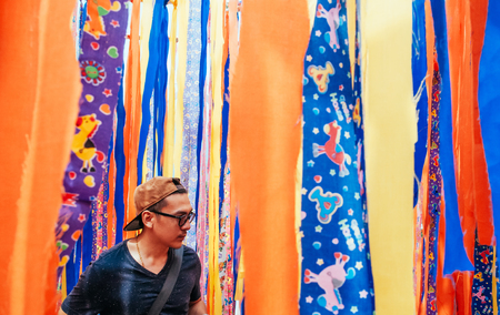 Young asian man stand with colorful vibrant vivid fabric strips background. Super Bright fun colored clothes fabric 写真素材