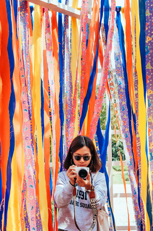 Young asian woman holding camera with Colorful vibrant vivid fabric strips background. Super Bright fun colored clothes fabric 写真素材