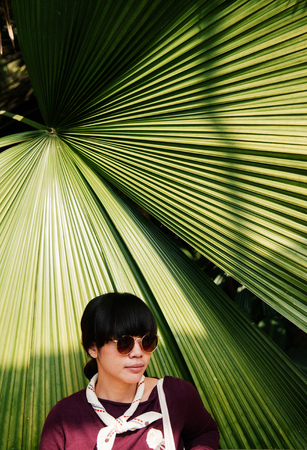 Street Fashion portrait of asian young woman wearing sunglasses with dark hair in jungle with large palm leaf background and warm sunlight