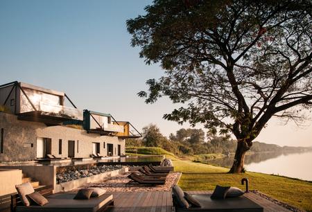 FEB 23, 2015 Kanchanaburi, Thailand : Beautiful modern loft vacation villa with balcony and pool by the river at X2 Resort in evening light - contemporary loft architecture design Редакционное