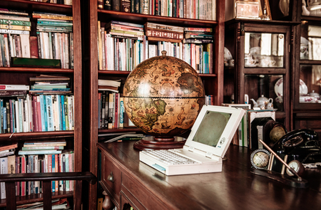 MAR 1, 2018 Uthaithani - Thailand : Retro rustic wooden vintage furniture interior decoration  concept vintage globe model and laptop computer in reading room