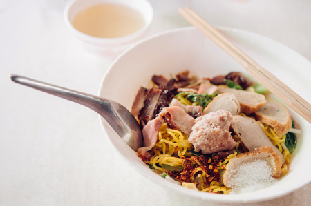 Thai egg noodle in white bowl - spoon -chopstick with sliced red barbecue pork, grounded pork ball, fish sausages, close up shot on white background