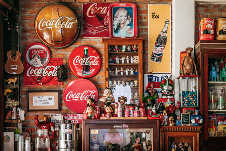 MAR 1, 2018 Uthaithani, Thailand : Vintage retro cola soda drink signage and retro vintage toy in brick wall room, wooden shelf