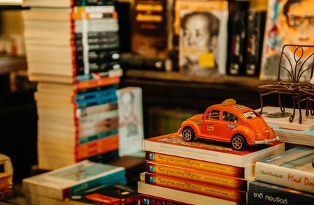MAR 1, 2018 Uthaithani, Thailand :  The Booktopia - Vintage retro local bookshop with orange colour vintage Volkswagen beetle taxi models on pile of book