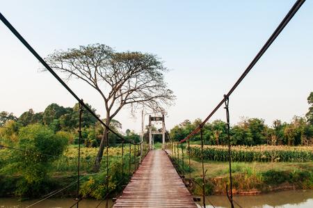 Old vintage wooden suspension bridge through cross over river in Koh Tepo, Uthaithani, Thailand