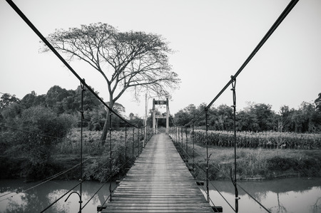 Old vintage wooden suspension bridge through cross over river in Koh Tepo, Uthaithani, Thailand