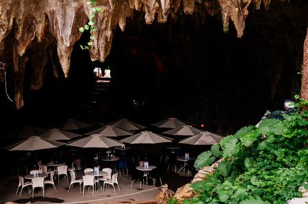 JAN 28, 2013 Naha, Okinawa, JAPAN : Oxotic Okinawa World Bunka Okoku Gyokusendo, Cave cafe tables and umbrellas in Gangala valley