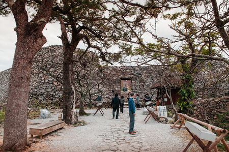 JAN 28, 2013 Naha, Okinawa, Japan : Ruin and remain of stone wall of Nakijin Gusuku castle remain with tree and tourist