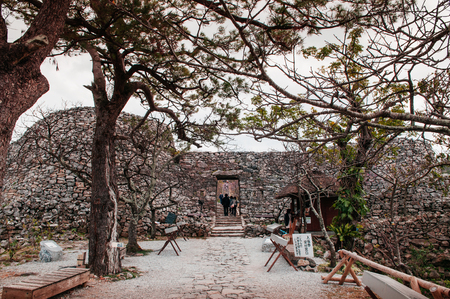 JAN 28, 2013 Naha, Okinawa, Japan : Ruin and remain of stone wall of Nakijin Gusuku castle remain with tree and tourists