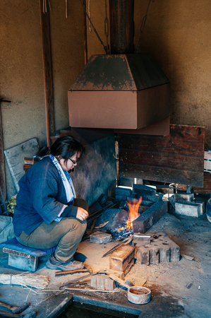 DEC 12, 2012 Chiba, JAPAN - Woker in blacksmith shop at Old traditional Edo Boso No Mura Open air museum, Edo town ancient village Editorial