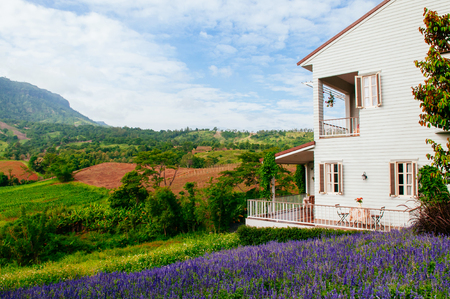 JUN 13, 2013 Thailand : Vintage English country house balcony with chairs and coffee table natural light mountain and flowers field