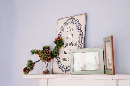 Wooden photo frame vintage home decorating items and conifer pine cone on wooden shelf pastel color wall 写真素材