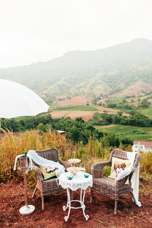 Afternoon tea vintage picnic furniture set on hill with mountain view 写真素材