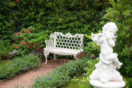 Vintage English country garden with flowers, white iron bench and cupid sculpture