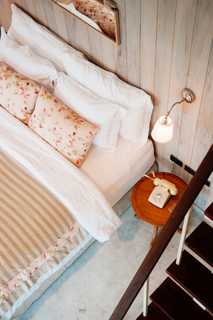 JUN 13, 2013 Thailand : English country vintage bedroom interior with natural light through window, pillow, wooden furniture, wall ornaments decoration