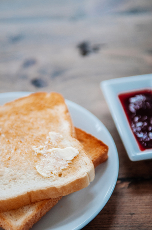 Beautiful Slice of toasted bread with butter and fruit jam, close up shot 写真素材