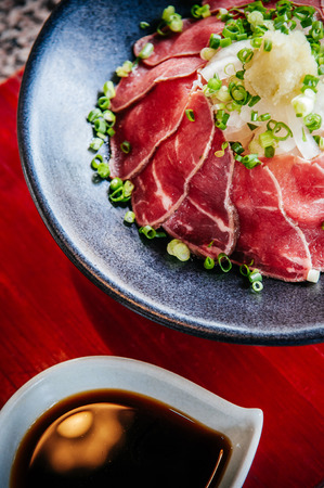 Beautiful Japanese Tataki raw beef cuisine in black bowl with ginger, onion, spring onion and soy sauce set on stone table 写真素材