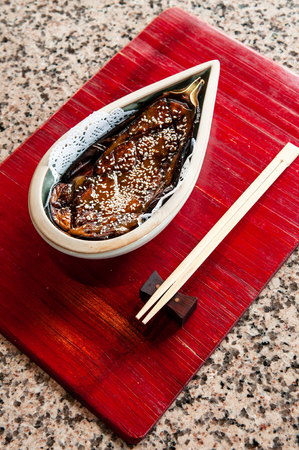 A beautiful piece of Japanese grilled eggplant recipe with sweetened miso sauce on red wooden tray 写真素材