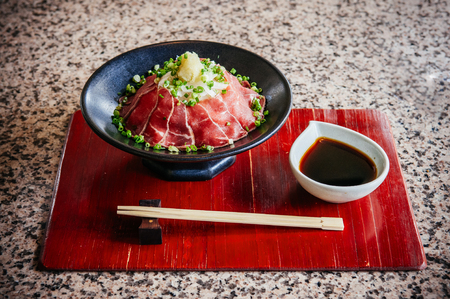 Beautiful Japanese Tataki raw beef cuisine with ginger, onion, spring onion and soy sauce set on red wooden tray and chopstick 写真素材