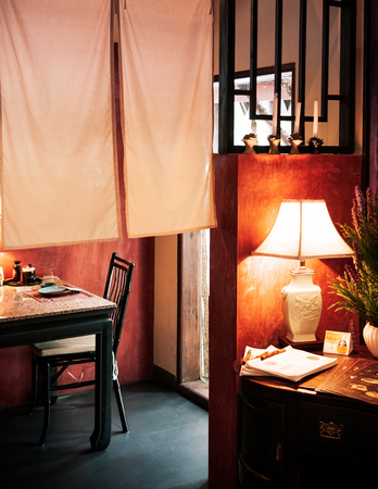 JUN 5, 2013 Chiang Mai, THAILAND - Nice vintage Chinese interior style dinning room with lamp, table, wooden chair and curtain. warm light
