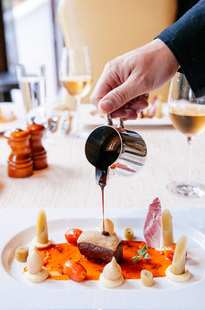 Pouring sweet and sour balsamic sauce on crispy Roasted duck breast