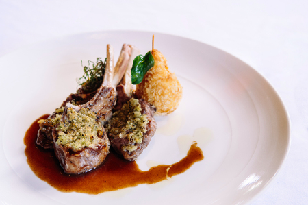 Waiter serving grilled lamb chops with crust, gravy and deep fried potato, close up shot 写真素材