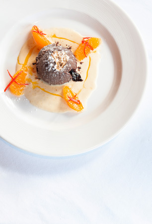 French dessert. Chocolate fondant lava cake with vanilla sauce, citrus and gold leaf on white plate top view 写真素材